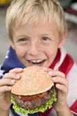Small boy holding hamburger (4th of July, USA)