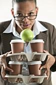 Geschäftsfrau hält vier Kaffeebecher und einen Apfel