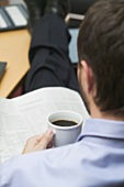 Businessman drinking coffee while reading newspaper in office