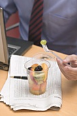 Businessman eating fruit salad in office