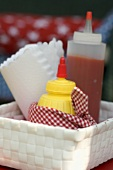 Bottle of ketchup, mustard and paper napkins in basket