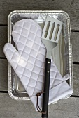 Barbecue glove and spatula in aluminium tray