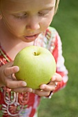 Small girl holding a large green apple