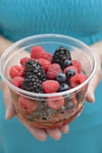 Woman holding plastic tub of fresh berries