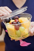 Woman holding plastic tub of fruit salad