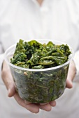 Woman holding plastic tub of cooked kale