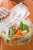 Woman holding plastic container of vegetables