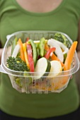 Woman holding plastic container of sliced vegetables
