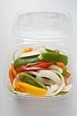 Sliced vegetables in opened plastic container (overhead)