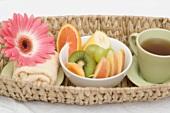 Cup of tea, fresh fruit, towel and flower in basket