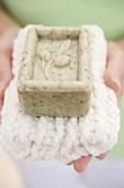 Frau hält Olivenseife auf Handtuch
