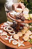 Hand reaching for Christmas biscuits on tiered stand