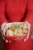 Woman holding dish of roasted onions (Christmas)