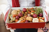 Woman holding roasting dish full of roasted root vegetables
