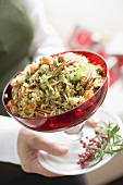 Woman holding bowl of vegetable rice with pecans (Christmas)