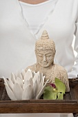 Woman holding statue of Buddha, candle and orchid on tray