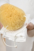 Hands holding bath sponge on white towel