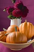 Four orange pumpkins in bowl, flowers in background