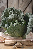 Savoy cabbage on chopping board in front of wooden wall