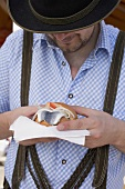 Man eating herring roll at Oktoberfest