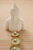 Three windlights in front of Buddha statue on bamboo mat