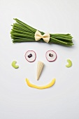 Amusing face made from vegetables, baby corn cob & chives