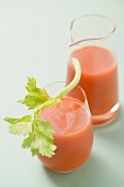 Glass of carrot juice with celery, jug in background