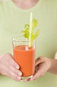 Woman holding glass of carrot juice with celery and straw