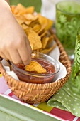 Child's hand dipping tortilla chip in salsa