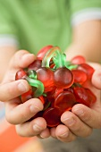 Child's hands holding cherry jelly sweets