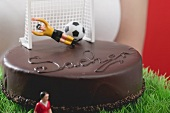 Woman holding Sacher torte with football figures