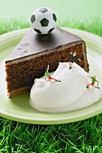 Piece of Sacher torte with cream and toy football