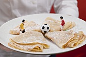 Woman serving plate of sweet crêpes with football figures