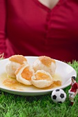 Woman serving apricot dumplings with football figure & football