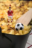 Cheese & onion pasta bake, football figure & football (detail)