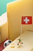 Swiss cheese with football figure, football and flag