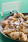Kaiserschmarren (Emperor's pancake) in pan with toy footballers