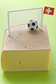 Swiss raclette cheese with football decoration and flag