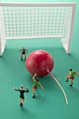 Toy footballers with radish in front of goal