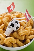 Peanut puffs with football whistle and flags in bowl