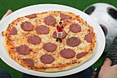 Hands holding salami pizza with toy footballer and remote