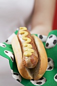 Woman holding hot dog with mustard on napkin with football motifs