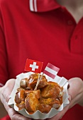 Woman holding currywurst with two flags in paper dish