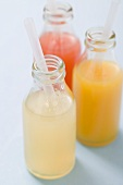 Three fruit juices in bottles with straws