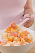 Woman taking spoonful of fruit salad out of bowl