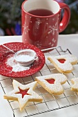 Jam biscuits on cake rack, icing sugar, mug of tea