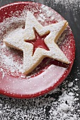 Jam biscuit with icing sugar on red plate