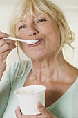 Woman eating yoghurt out of plastic pot