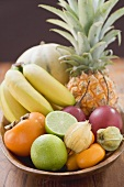 Exotic fruit and citrus fruit in wooden bowl