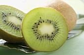 Two halves of a kiwi fruit in front of whole kiwi fruit